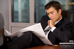 Journal de lecture d'homme d'affaires dans le bureau avec la main sur le menton Images stock