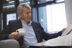 Journal de lecture d'homme d'affaires tout en ayant le café Images stock