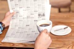 Journal de lecture d'homme et café potable Image stock