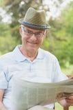 Journal de lecture d'homme supérieur au parc Photos stock