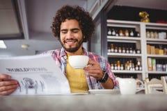 Journal de lecture d'homme tout en ayant le café Photo stock
