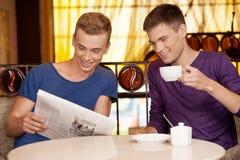 Journal de lecture de deux jeunes hommes Photographie stock libre de droits