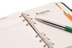 Journal et crayon lecteur ouverts sur le fond blanc Photographie stock libre de droits