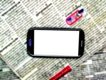 Journal et Smartphone de tache floue images stock