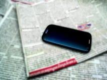 Journal et Smartphone de tache floue photographie stock libre de droits