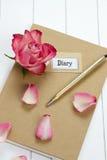 Journal intime avec la rose et les feuilles de rouge Photos stock