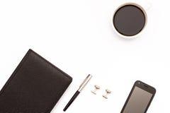 Journal intime, boutons de manchette, stylo, smartphone et tasse noirs de café noir sur un fond blanc Lieu de travail minimal de  Image stock