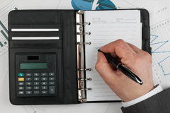 Journal intime, calculatrice, main et stylo Images stock