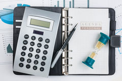 Journal intime, calculatrice, sablier et stylo Image stock