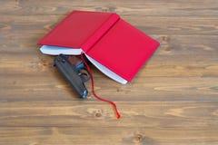 Journal intime dans la peau rouge une arme à feu sur la table Photographie stock libre de droits