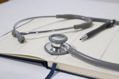 Journal intime de stéthoscope et de carnet sur le fonctionnement de table du docteur, medis image stock