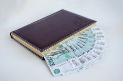 Journal intime et billets de banque sur le fond blanc Image libre de droits