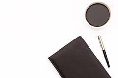 Journal intime noir, stylo et une tasse de café noir sur un fond blanc Concept minimal d'affaires pour le lieu de travail dans le Photos libres de droits