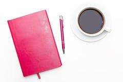 Journal intime rose avec le stylo et une tasse de café noir sur le fond blanc Image stock