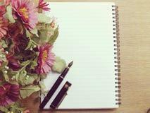 Journal intime vide de carnet avec la fleur rose sur le fond en bois Photos stock