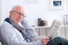 Journal mûr beau de lecture d'homme sur le sofa Photos stock