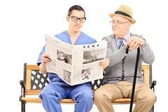 Journal masculin de lecture d'infirmière à un monsieur plus âgé Photographie stock libre de droits