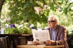 Journal moderne de lecture d'homme supérieur en café extérieur Photographie stock