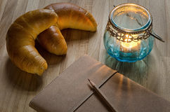 Journal, old candle lantern and croissants Royalty Free Stock Images
