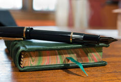 Journal and pen on desk. Closeup of a green, leather-bound journal with pen resting on top; shallow depth of field Stock Photos