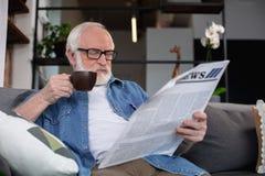 Journal retiré concentré de lecture d'homme avec du café Photos stock
