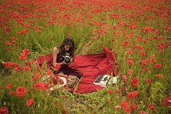 Journalism and writing, summer. Poppy, Remembrance or Anzac Day. Drug, narcotics, opium, woman with typewriter, camera, book. Woman writer in poppy flower stock photography