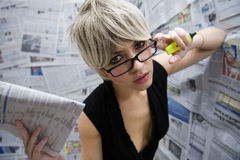 Journalist. Women at work: journalist standing against a wall full of articles Stock Photos