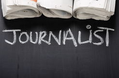 Journalist. The word Journalist written on a blackboard next to rolled up newspapers, with copy space Royalty Free Stock Photo