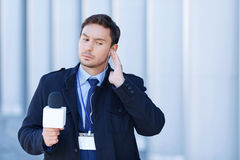 Journalist checks his gadgets before broadcast Royalty Free Stock Photo