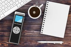 Journalist Digital Voice Recorder or Dictaphone, Keyboard, Blank. Note Pad with Pen and Cup of Coffee on a wooden table. 3d Rendering Stock Photo