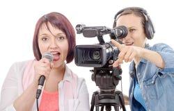 Journalist för ung kvinna med en mikrofon och en camerawoman Arkivbild