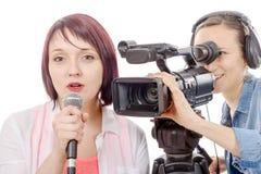 Journalist för ung kvinna med en mikrofon och en camerawoman Fotografering för Bildbyråer
