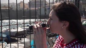 Journalist het letten op verrekijkers door de omheining stock video