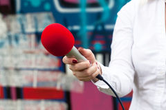 Journalist holding a microphone conducting an media interview Stock Photography