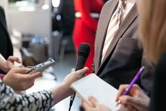 Journalist holding microphone conducting media interview. Reporter holding microphone conducting press interview Stock Photo
