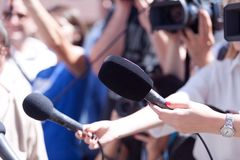 Journalist holding microphone conducting media interview. Reporter holding microphone conducting press interview Royalty Free Stock Image