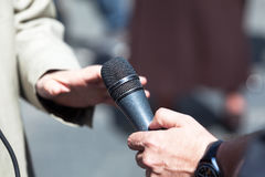Journalist holding a microphone conducting an TV or radio interview. Reporter holding a microphone conducting an media interview Royalty Free Stock Image