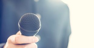 Journalist is holding a microphone in the foreground, blurry background. Interview: Black microphone in the foreground, man with blue shirt in the blurry stock image