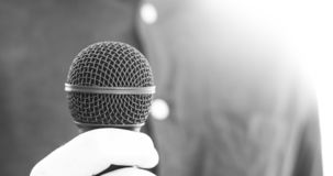 Journalist is holding a microphone in the foreground, blurry background. Interview: Black microphone in the foreground, man with blue shirt in the blurry stock photos