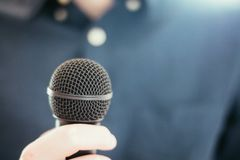 Journalist is holding a microphone in the foreground, blurry background. Interview: Black microphone in the foreground, man with blue shirt in the blurry stock photography
