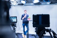 Free Journalist In A Television Studio Is Talking Into A Microphone, Blurry Film Cameras Royalty Free Stock Images - 146642969