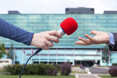 Journalist interviewing businessperson, corporate building in background Royalty Free Stock Photography