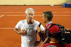 Journalist interviewing John McEnroe after a tennis match. Statements to the press of McEnroe after a tennis match of senior category Stock Photo