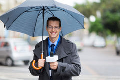 Journalist live broadcasting. Male journalist holding umbrella and live broadcasting in the rain Stock Photo