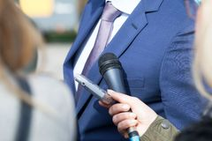 Politician or business person giving statement to journalists at press conference stock images