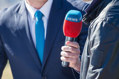 Journalist with microphone interviewing. News journalist with microphone interviewing Stock Image