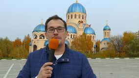 Journalist mit Mikrofon vor Kirche stock footage
