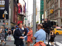 Journalist N J Burkett som anmäler från Times Square, ögonvittnenyheterna, NYC, USA Arkivbild