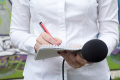 Journalist. News conference. Media interview. Female reporter or journalist at news conference, writing notes, holding microphone Royalty Free Stock Photo