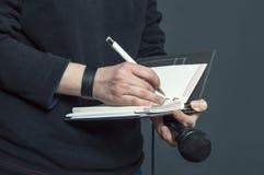 Journalist på presskonferensen som skriver anmärkningar, hållande mikrofon Arkivfoton